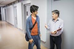 Καθηγητής με το σημειωματάριο που μιλά σε έναν σπουδαστή Στοκ φωτογραφίες με δικαίωμα ελεύθερης χρήσης