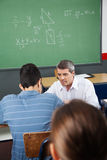 Καθηγητής Assisting Student While Crouching στοκ εικόνες