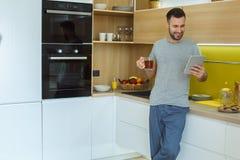 Καθημερινή ρουτίνα ατόμων αγάμων σε μια ενιαία έννοια τρόπου ζωής κουζινών που πίνει το καυτό τσάι που χρησιμοποιεί την ψηφιακή τ στοκ φωτογραφίες με δικαίωμα ελεύθερης χρήσης