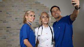 Καθημερινή ρουτίνα των γιατρών Τρεις ιατρικοί εργαζόμενοι που κάνουν selfie από κοινού χαμόγελο γιατρών 4 Κ απόθεμα βίντεο