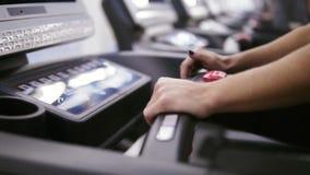 Καθιέρωση γυναικών bodbuilder ένα πρόγραμμα και ένα χρονόμετρο treadmill που τίθεται στη γυμναστική που προετοιμάζεται να αρχίσει φιλμ μικρού μήκους