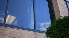 Καθιέρωση του πυροβολισμού μιας πρώτης θέσης γραφείων ιστορίας πίσω από ένα παράθυρο στη στο κέντρο της πόλης περιοχή απόθεμα βίντεο