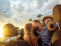 Καθιερώνον τη μόδα νέο ζεύγος που έχει μια τρυφερή στιγμή στο μετατρέψιμο αυτοκίνητο κατά τη διάρκεια του οδικού ταξιδιού τους -  στοκ φωτογραφίες