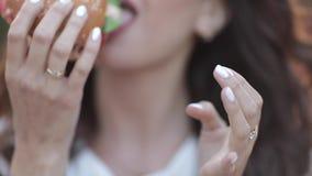 Καθιερώνον τη μόδα νέο κορίτσι στα γυαλιά που τρώει το νόστιμο χάμπουργκερ απόθεμα βίντεο