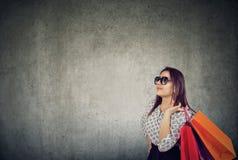 Καθιερώνον τη μόδα νέο brunette στα γυαλιά ηλίου που κρατούν τις τσάντες αγορών στοκ φωτογραφίες με δικαίωμα ελεύθερης χρήσης
