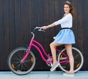 Καθιερώνον τη μόδα μοντέρνο κορίτσι με το εκλεκτής ποιότητας ποδήλατο στο μαύρο ξύλινο υπόβαθρο φωτογραφία που τονίζετα&i Σύγχρον Στοκ Εικόνες
