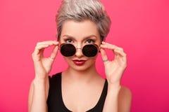 Καθιερώνον τη μόδα νέο πορτρέτο γυναικών με την κοντή τρίχα και τα στρογγυλά γυαλιά ηλίου Στοκ Εικόνες