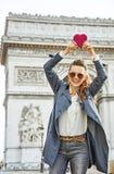 Καθιερώνουσα τη μόδα γυναίκα κοντά Arc de Triomphe που παρουσιάζει κόκκινη καρδιά Στοκ φωτογραφίες με δικαίωμα ελεύθερης χρήσης