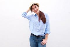 Καθιερώνουσα τη μόδα ευτυχής γυναίκα που στέκεται με το χέρι στο καπέλο στοκ φωτογραφία με δικαίωμα ελεύθερης χρήσης