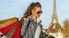 Καθιερώνουσα τη μόδα γυναίκα με τις τσάντες αγορών που γράφει sms κοντά στον πύργο του Άιφελ Στοκ φωτογραφία με δικαίωμα ελεύθερης χρήσης