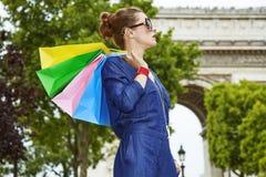 Καθιερώνουσα τη μόδα γυναίκα με τις τσάντες αγορών που κοιτάζει κατά μέρος στο Παρίσι, Γαλλία Στοκ Φωτογραφία