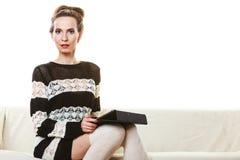 Καθιερώνουσα τη μόδα γυναίκα μόδας με την ταμπλέτα στο σπίτι στοκ εικόνα