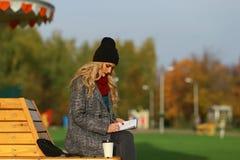 Καθιερώνουσα τη μόδα γυναίκα στη μοντέρνη συνεδρίαση παλτών στον πάγκο στο πάρκο πόλεων Αστική σκηνή υπαίθρια Στοκ Φωτογραφία