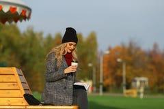 Καθιερώνουσα τη μόδα γυναίκα στη μοντέρνη συνεδρίαση παλτών στον πάγκο στο πάρκο πόλεων Αστική σκηνή υπαίθρια Στοκ εικόνα με δικαίωμα ελεύθερης χρήσης