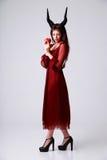 Καθιερώνουσα τη μόδα γυναίκα στο κόκκινο φόρεμα με το μήλο Στοκ Εικόνες