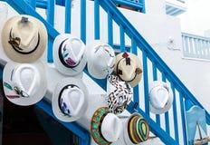 Καθιερώνουσα τη μόδα ελληνική συλλογή θερινών καπέλων σε μια χαρακτηριστική οδό της Μυκόνου, ελληνικά νησιά Στοκ Εικόνες