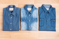 Καθιερώνουσα τη μόδα μόδα πουκάμισων τζιν στην ξύλινη άποψη επιτραπέζιων κορυφών Στοκ εικόνα με δικαίωμα ελεύθερης χρήσης