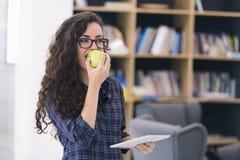 Καθιερώνουσα τη μόδα νέα γυναίκα που τρώει ένα πράσινο μήλο Πέρα από το υπόβαθρο βιβλιοθηκών Στοκ εικόνες με δικαίωμα ελεύθερης χρήσης