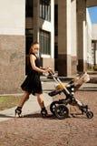 Καθιερώνουσα τη μόδα σύγχρονη μητέρα σε μια οδό πόλεων με ένα καροτσάκι. Νέα μητέρα Στοκ Φωτογραφία