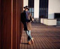 Καθιερώνων τη μόδα όμορφος νεαρός άνδρας στη μόδα φθινοπώρου που στέκεται στο αστικό περιβάλλον Στοκ Φωτογραφίες