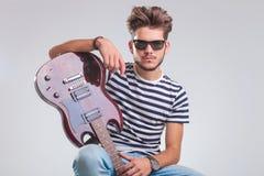 Καθισμένο άτομο με την κιθάρα που στηρίζεται θέτοντας στο στούντιο Στοκ Φωτογραφίες