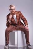 Καθισμένο άτομο μόδας με τη γενειάδα και τα γυαλιά στοκ φωτογραφίες