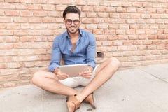 Καθισμένο περιστασιακό άτομο με ένα χαμόγελο μαξιλαριών ταμπλετών Στοκ εικόνα με δικαίωμα ελεύθερης χρήσης