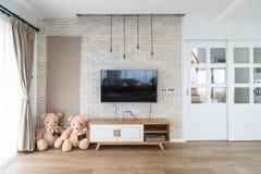 Καθιστικό με την οδηγημένη TV στο τουβλότοιχο και τον ξύλινο πίνακα στοκ εικόνες