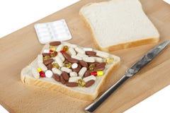 Καθιστώντας ένα νόστιμο σάντουιτς γεμισμένο με τα χάπια και τις ταμπλέτες Στοκ εικόνες με δικαίωμα ελεύθερης χρήσης