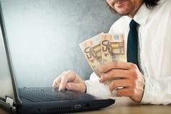 Καθιστώντας τα χρήματα σε απευθείας σύνδεση, επιχειρηματίας με το φορητό προσωπικό υπολογιστή Στοκ Εικόνες