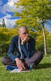 Καθμένος νεαρός άνδρας με το βιβλίο στο πάρκο Στοκ φωτογραφία με δικαίωμα ελεύθερης χρήσης