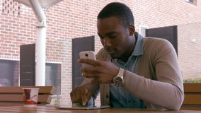 Καθμένος νεαρός άνδρας που χρησιμοποιεί το smartphone και την ταμπλέτα φιλμ μικρού μήκους