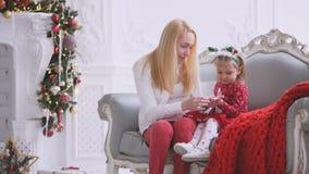 Καθμένος στον καναπέ από την εστία με ένα ντεκόρ Χριστουγέννων, τη γυναίκα και την λίγη κόρη έχει να κουβεντιάσει διασκέδασης απόθεμα βίντεο