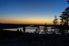Καθμένος στο ηλιοβασίλεμα, στην άκρη του απότομου βράχου και του κοιτάγματος έξω στην απόσταση στη λίμνη Στοκ φωτογραφία με δικαίωμα ελεύθερης χρήσης