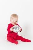 Καθμένος χαμογελώντας μωρό στο κόκκινο με τη σφαίρα συμβαλλόμενων μερών Στοκ φωτογραφία με δικαίωμα ελεύθερης χρήσης