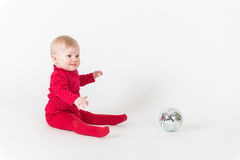 Καθμένος χαμογελώντας μωρό στο κόκκινο με τη σφαίρα συμβαλλόμενων μερών Στοκ Φωτογραφίες