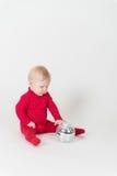 Καθμένος χαμογελώντας μωρό στο κόκκινο με τη σφαίρα συμβαλλόμενων μερών Στοκ εικόνα με δικαίωμα ελεύθερης χρήσης