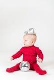 Καθμένος χαμογελώντας μωρό στο κόκκινο με τη σφαίρα συμβαλλόμενων μερών Στοκ Φωτογραφία
