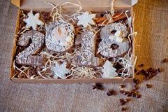 Καθορισμένα μπισκότα μελιού, τυποποιημένα ως ξύλινους αριθμούς 2, 0, 1, 8 και άσπρα αστέρια που βάζουν στο κιβώτιο εγγράφου καφετ Στοκ Φωτογραφία