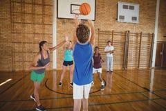 Καθορισμένα παιδιά γυμνασίου που παίζουν την καλαθοσφαίριση Στοκ φωτογραφία με δικαίωμα ελεύθερης χρήσης