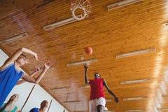 Καθορισμένα παιδιά γυμνασίου που παίζουν την καλαθοσφαίριση Στοκ Εικόνες
