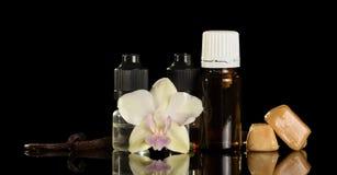Καθορισμένα υγρά την περιοχή, το λουλούδι και το λοβό της βανίλιας, που απομονώνονται που καπνίζουν στο Μαύρο Στοκ Φωτογραφία
