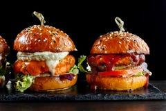 Καθορισμένα burgers με το βόειο κρέας Σε μια μαύρη ανασκόπηση Στοκ εικόνα με δικαίωμα ελεύθερης χρήσης