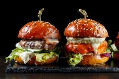 Καθορισμένα burgers με το βόειο κρέας Σε μια μαύρη ανασκόπηση Στοκ φωτογραφίες με δικαίωμα ελεύθερης χρήσης
