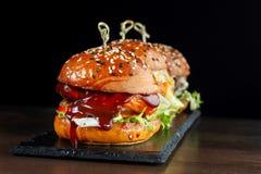 Καθορισμένα burgers με το βόειο κρέας Σε μια μαύρη ανασκόπηση Στοκ Φωτογραφίες