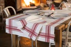 Καθορισμένα Dinnerware και τραπεζομάντιλο με τα κόκκινα λωρίδες που καίγονται πλησίον την πυρκαγιά Στοκ εικόνες με δικαίωμα ελεύθερης χρήσης