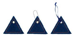 Καθορισμένες ετικέττες Jean υπό μορφή τριγώνων με τα καρφιά μετάλλων Στοκ Φωτογραφία