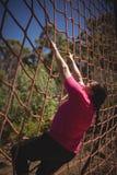 Καθορισμένη γυναίκα που αναρριχείται σε ένα δίχτυ κατά τη διάρκεια της σειράς μαθημάτων εμποδίων Στοκ εικόνα με δικαίωμα ελεύθερης χρήσης
