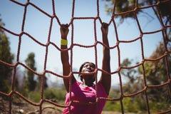 Καθορισμένη γυναίκα που αναρριχείται σε ένα δίχτυ κατά τη διάρκεια της σειράς μαθημάτων εμποδίων Στοκ Εικόνες