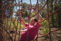 Καθορισμένη γυναίκα που αναρριχείται σε ένα δίχτυ κατά τη διάρκεια της σειράς μαθημάτων εμποδίων Στοκ φωτογραφία με δικαίωμα ελεύθερης χρήσης